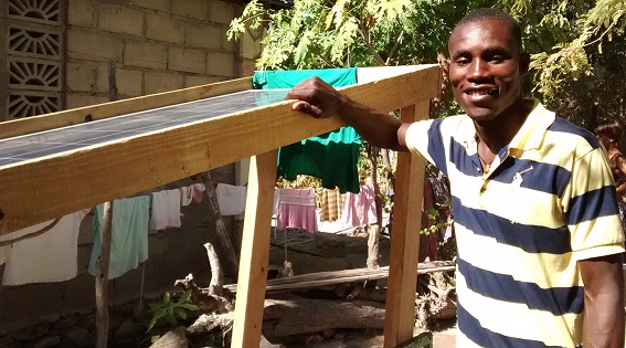 Robenson next to the solar stand he built for charging the XOs