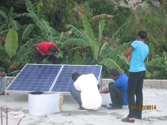 The team affixes the solar panel while Jeanide looks on.